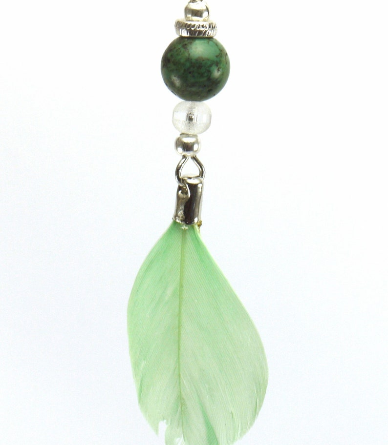 silver metal and pale green feather. Turquoise pearl earrings and transparent glass beads