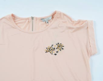 Embroidered yellow and black stars on pink tee. Cute wearable embroidery design