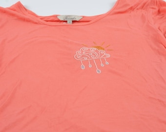 Embroidered sun, cloud, and rain on pink tee. Colourful weather wearable embroidery design