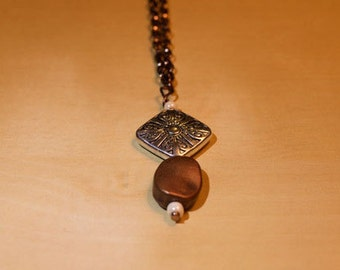 Antique Silver and Copper Pendant Necklace on an Antique Bronze