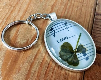 """Genuine four-leaf clover keychain with Beatles sheet music (""""All You Need Is Love"""")"""