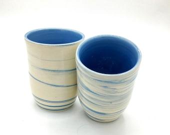 Handmade wheel thrown stoneware water cups with blue swirl.