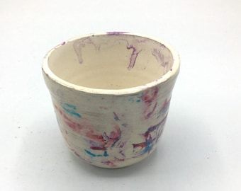 Wheel thrown earthenware tea cup with ribbons of reds blues and purples.