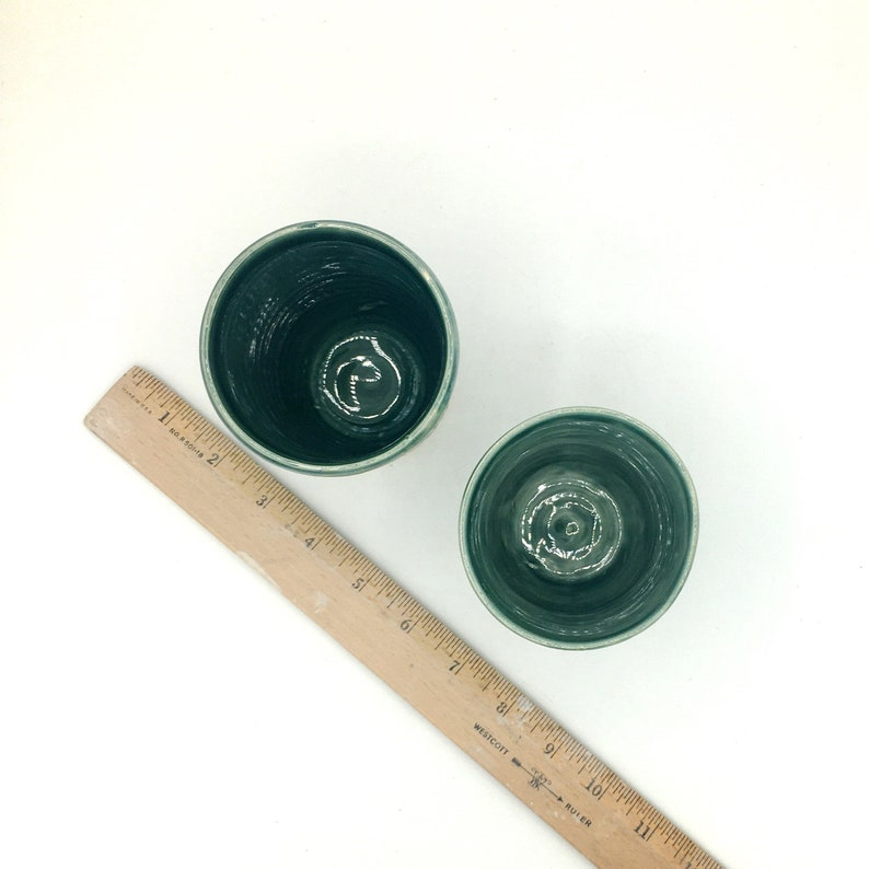 Handmade wheel thrown stoneware cups with carved texture in green.