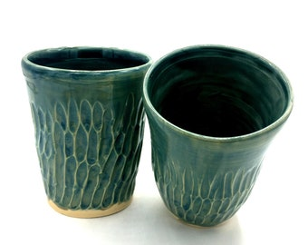 Handmade wheel thrown stoneware cup with carved texture in green.