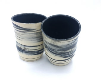 Handmade whee thrown stoneware tumblers with black and white marbled clay and a black interior
