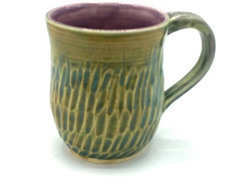 Handmade wheel thrown stoneware coffee or tea mug with carved texture in a green blue with mauve inside.