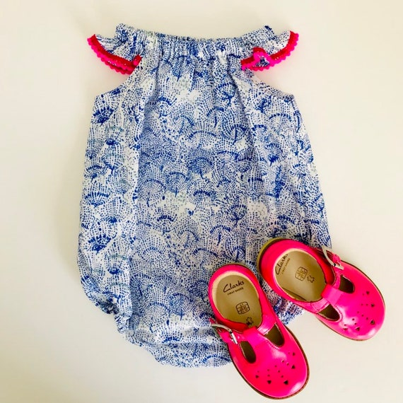 "Eddie & Bee flutter sleeve romper in royal  blue and silver ""Sea shells"" print Japanese double gauze cotton with neon pink Pom Pom trim."