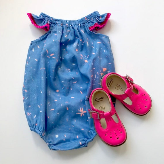 "Eddie & Bee flutter sleeve romper in Blue/ pink ""Spring Blossom"" cotton double gauze with neon pink pompom trim."