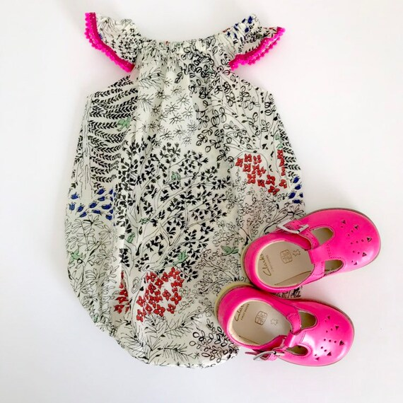"Eddie & Bee flutter sleeve romper in  cream ""birds of paradise"" print Japanese cotton voile with neon pink Pom Pom trim."