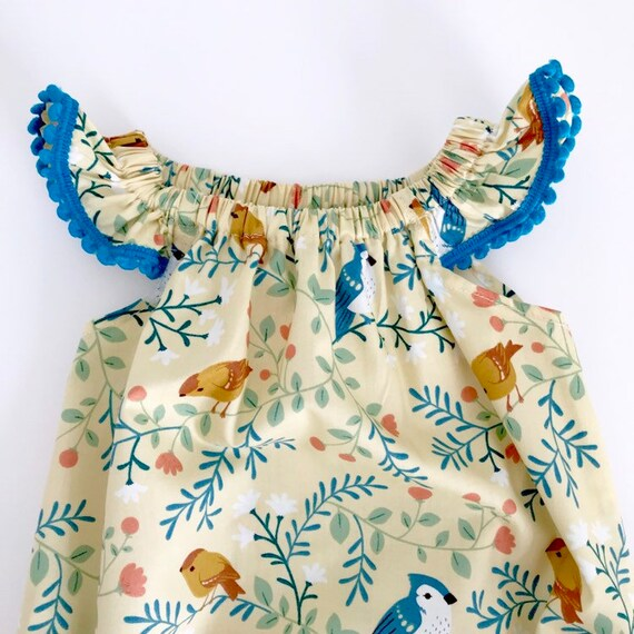 "Eddie & Bee flutter sleeve romper in cream ""perching birds"" print organic cotton with teal  Pom Pom trim."