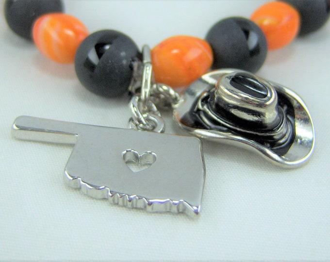B293 - Orange and Black Glass Beads with Oklahoma and Cowboy Hat Charm Bracelet