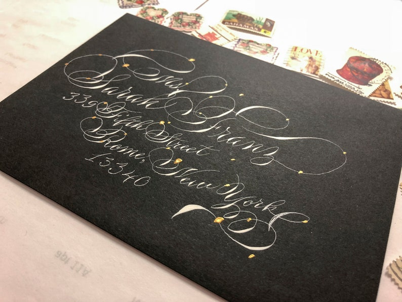 Gold dotted black A7 envelopes with white ink in highly flourished calligraphy Black wedding envelopes fancy handwriting Gala script