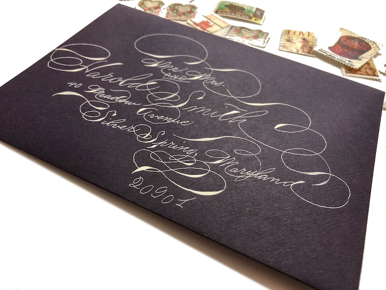 Purple A7 envelopes with white ink in highly flourished calligraphy stylish fun Handwritten wedding envelopes Spencerian script