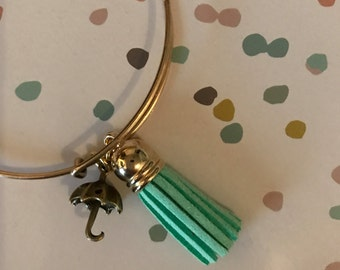 Adjustable goldtone bangle with umbrella charm and turquoise tassel