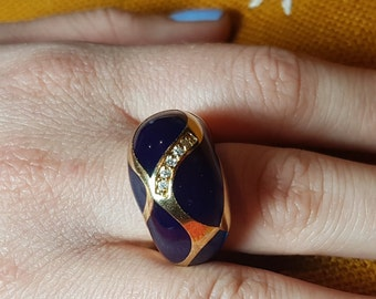 Gold plated ring with navy blue finished details.
