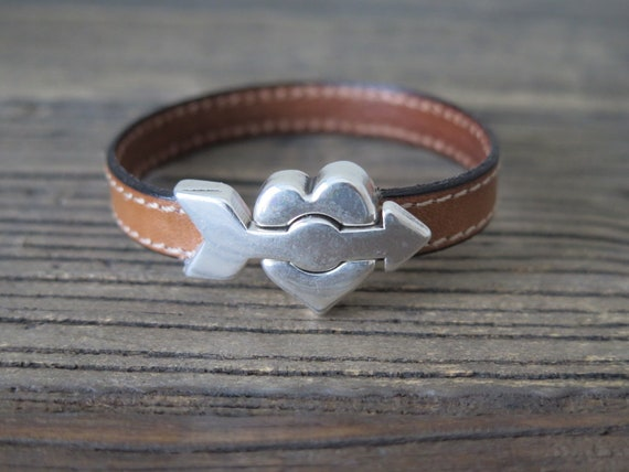 "7 1/2"" hand made 10mm stitched leather cuff accented with ""Arrow through heart"" magnetic clasp"