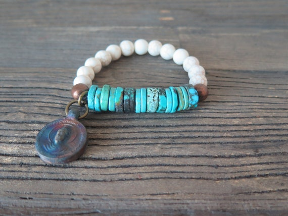 Hand beaded 15mm Heishi Turquoise, natural howlite, and vintage copper findigs accented with a ceramic Relic charm