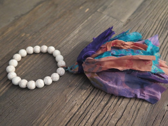 Hand beaded 10mm matte natural howlite bracelet accented with a hand made Sari silk tassel