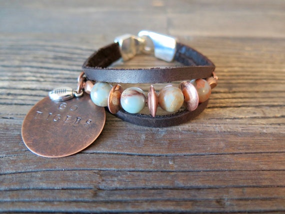 "Hand made leather cuff accented with 10mm Snake skin Jasper copper heishi beads and a hand stamped ""Go Tigers"" vintage copper charm."