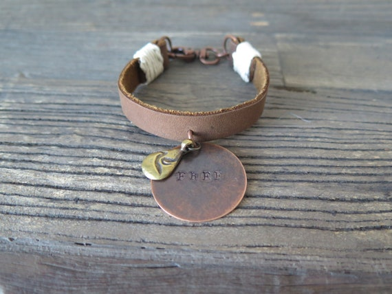 """Hand made leather cuff accented with a hand stamped """"Free"""" charm and bronze bird charm"""