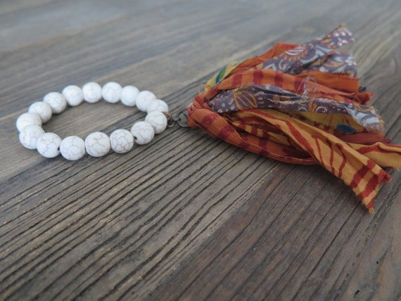 Hand beaded 12mm natural Howlite bracelet accented with a Sari Silk tassel