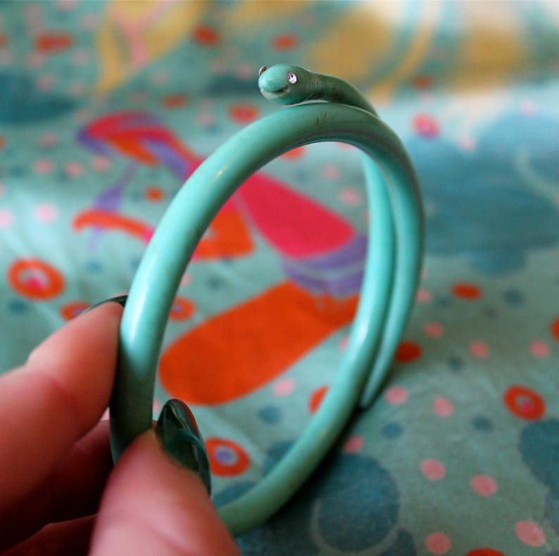 20s plastic turquoise serpent bangle with rhinestone eyes and carved happy smile 1920s celluloid smiling snake bracelet