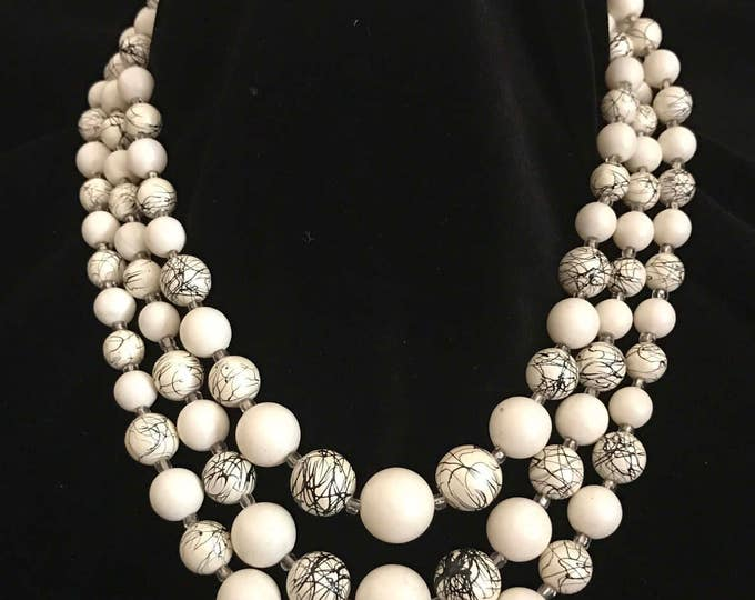 "Three strand off white and black beaded necklace marked ""Japan"""