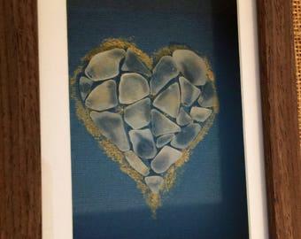 White seaglass heart on navy backround framed.