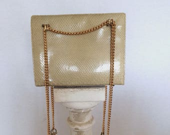 Elegant chic 1960s vintage reptile purse with golden chains.