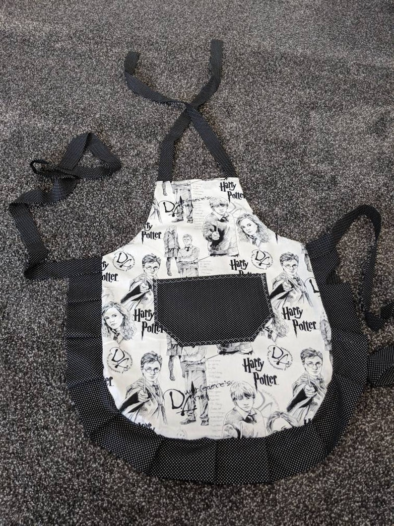 Harry Potter black images on white ties and frills. Black with mini black polka dots on pocket Girl/'s apron Youth apron