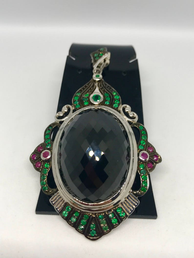 The huge black spinel surrounding with ruby and green sapphire sliver pendant