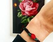 Fine crochet bracelet, base black with small rose. zoownatas