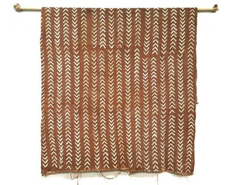 Rust mudcloth fabric throw w/ small arrow print