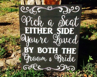Pick a seat either side you're loved by both the groom and bride ceremony seating sign, wedding sign, ceremony decor, wood wedding sign
