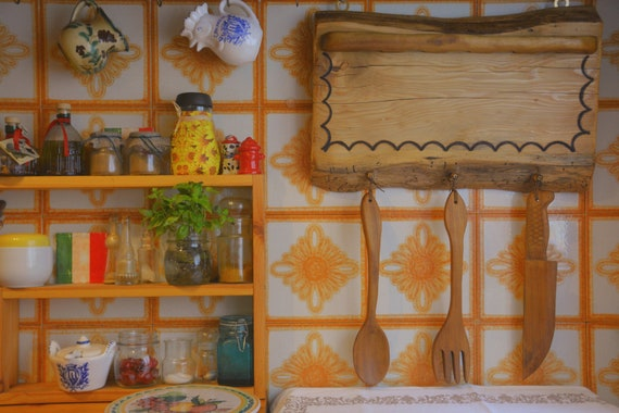 Rustic style wooden kitchen utensil rack with decorative utensils.