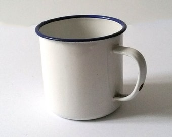 Old farmhouse white enamelware cup with blue trim