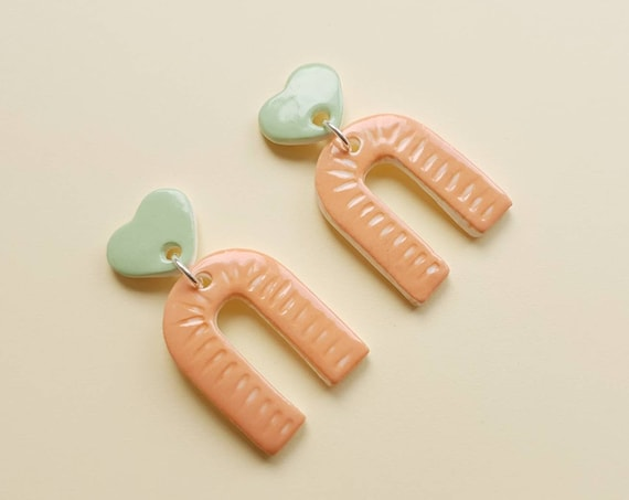 Statement arch dangles , green heart studs with orange/white carving, ceramic with sterling silver posts