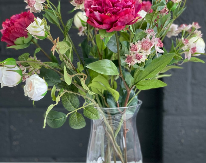 Deep pink peony and rose faux floral arrangement set into a glass vase