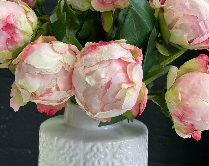 Stunning faux peony floral arrangement set into white ceramic vase