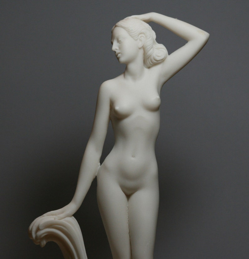 A bronze sculpture of a posing female nude
