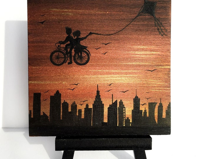 Kite bike ride above the city -  sunset - silhouette - miniature miniature limited edition print mounted on wood