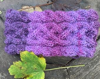 Hand knitted wool headband/ear warmer in Celtic knot pattern. Mixed purple colours. Fleece lined.