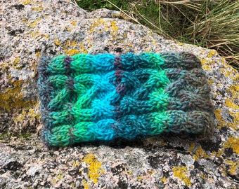 Hand knitted wool headband in Celtic knot pattern. Fleece lined