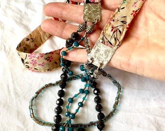 Mixed media multi strand necklace with silk fabric, sterling silver, faceted hematite and glass. 34 inches long.