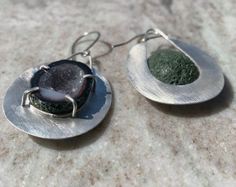 Crystal geodes set in sterling silver with a prong setting .