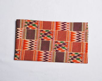 orange and blue african head wrap with kente pattern