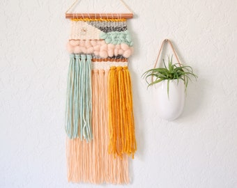 Blush and mint woven wall hanging. Copper and yellow accents with a natural stone detail. Made to order weaving.