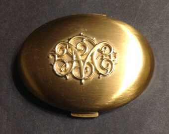 Germaine Monteil gold tone oval compact, filigree GM monogram on top of lid, name in script on powder puff.