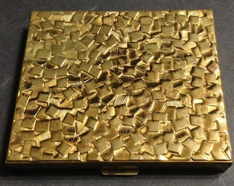 Gold tone Superglow Golden Nugget Germaine Monteil compact, small dimensional squares design, some textured and some smooth.